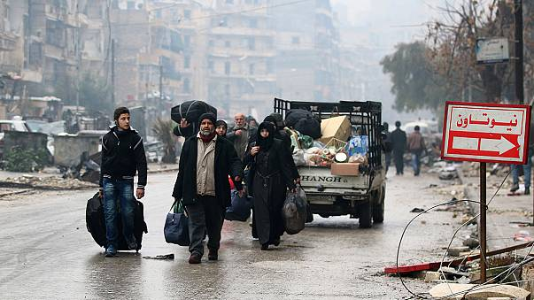 Thousands stream out of Aleppo as rebel deal is struck