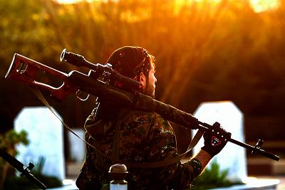 A fighter with the Syrian Democratic Forces holds a rifle on his shoulder as he attends a funeral on Dec. 6.