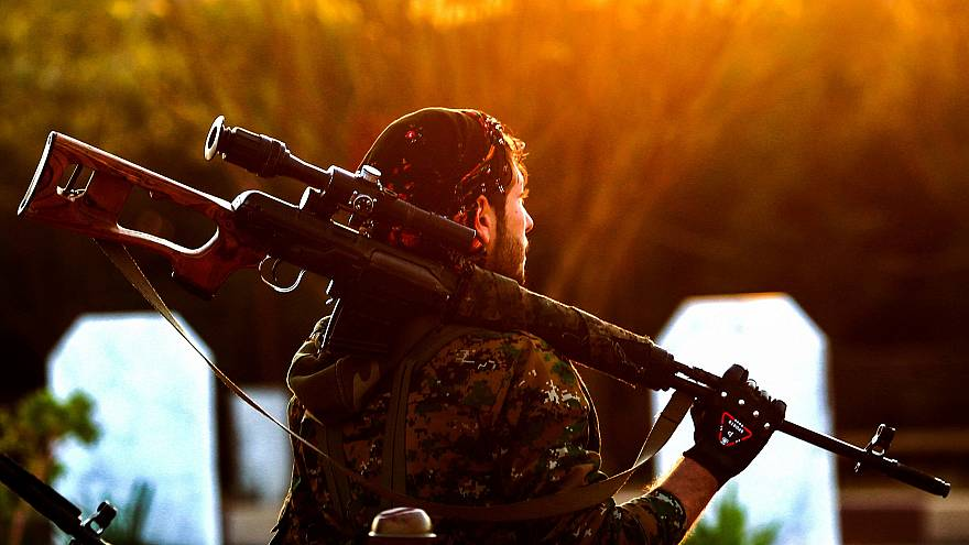 Image: A fighter with the Syrian Democratic Forces holds a rifle as he atte