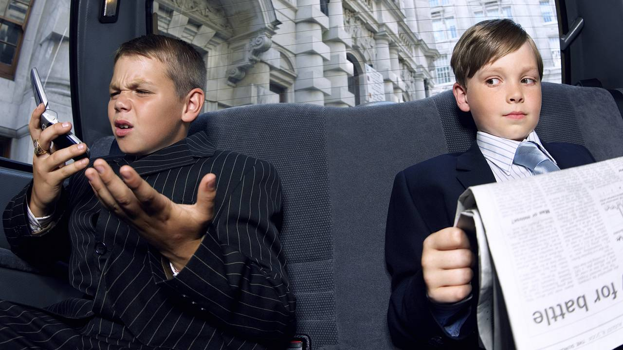 Boys dressed as businessmen in back of a car.