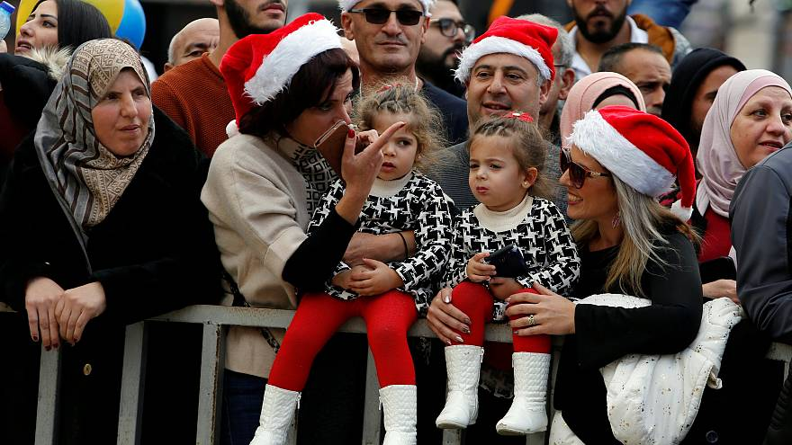 Image: People attend Christmas celebrations at Manger Square outside the Ch