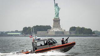 Image: A U.S. Coast Guard boat passes Liberty Island in New York Harbor on