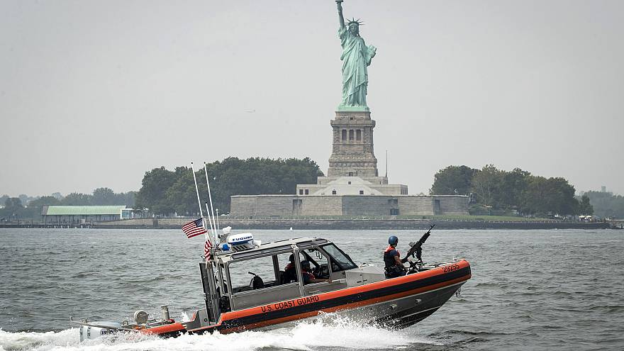 Image: A U.S. Coast Guard boat passes Liberty Island in New York Harbor on