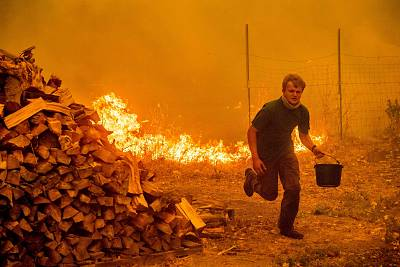 Alex Schenck carries a water bucket while fighting to save his home as the Ranch Fire rages near Clearlake Oaks, California, on  Aug. 4.
