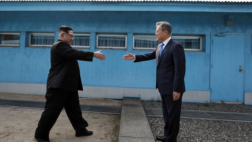 Image: Kim Jong Un and Moon Jae-in shake hands over the military demarcatio