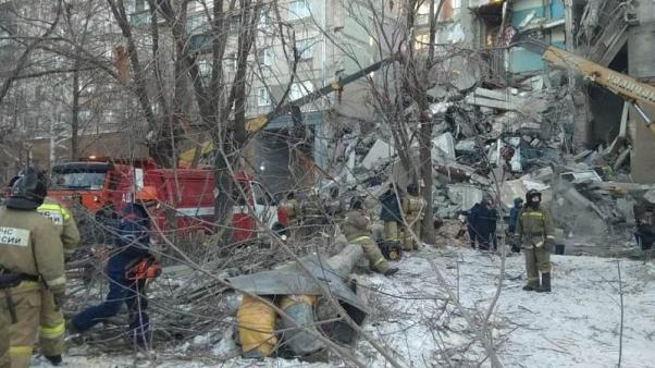Image: Emergency personnel work at the site of collapsed apartment building