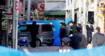 Police stand next to a car which plowed into pedestrians early on New Year\'d Day in Tokyo.