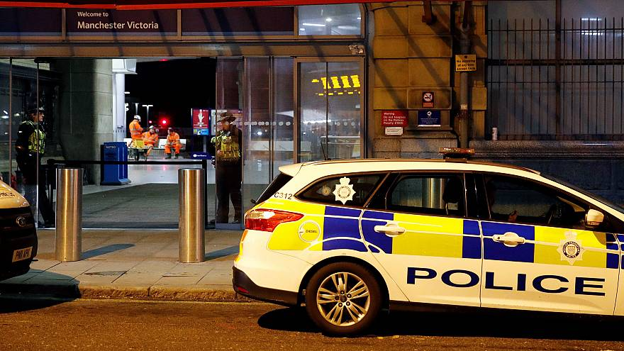 Image: Police officers stand at the end of a tram platform following a stab