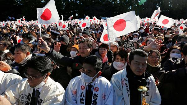 Image: Cheering crowds greet Japan's Emperor Akihito and other members of t