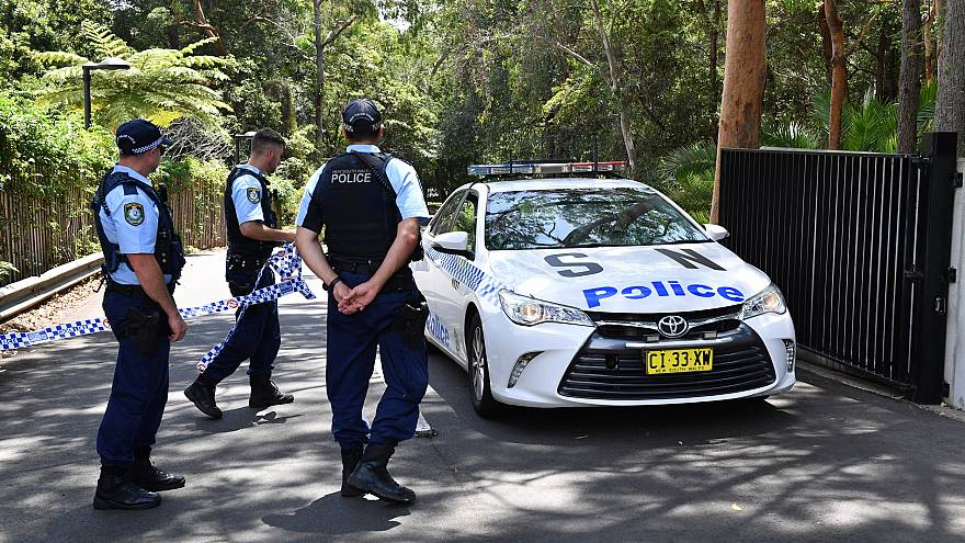 Image: New South Wales police stand guard at the scene of a stabbing at the