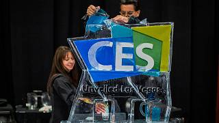 Image: Workers serve beverages from an ice sculpture during the Consumer El