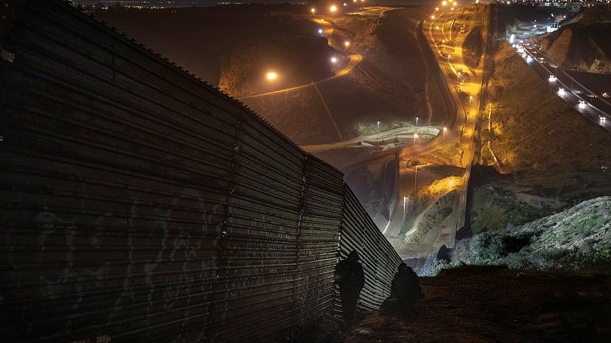 Image: Migrants looks for a place to jump over the border fence to enter th