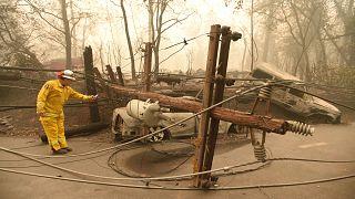 Image: CalFire firefighter Scott Wit surveys burnt out vehicles near a fall