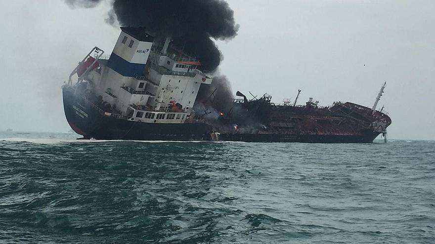 Image: Smoke rising from an oil tanker as it tilts to one side in the water