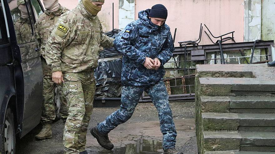 Image: A member of Russia's FSB security service escorts a detained Ukraini
