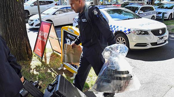 Image: A Victoria Police forensic officer carries items to be loaded into a