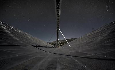 CHIME radio telescope (seen at night here) recently detected rare, low-frequency bursts of energy from deep in the universe. Astronomers are eagerly searching for an explanation.