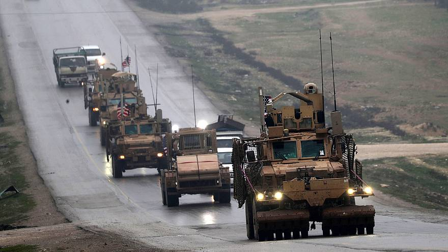 Image: A convoy of US military vehicles rides in Syria's northern city of M