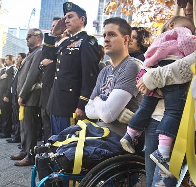 "Former U.S. Air Force Senior Airman Brian Kolfage, center, sits in a wheelchair next to his wife Ashley, right, who holds their daughter Paris, during the National September 11 Memorial and Museum\'s ""Salute to Service"" tribute honoring U.S. veterans in New York on Nov. 10, 2014."