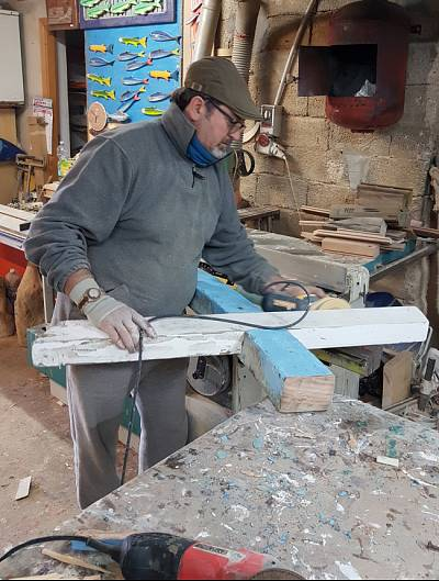 Francesco Tuccio uses wood salvaged from migrant boats to make crosses in his workshop.