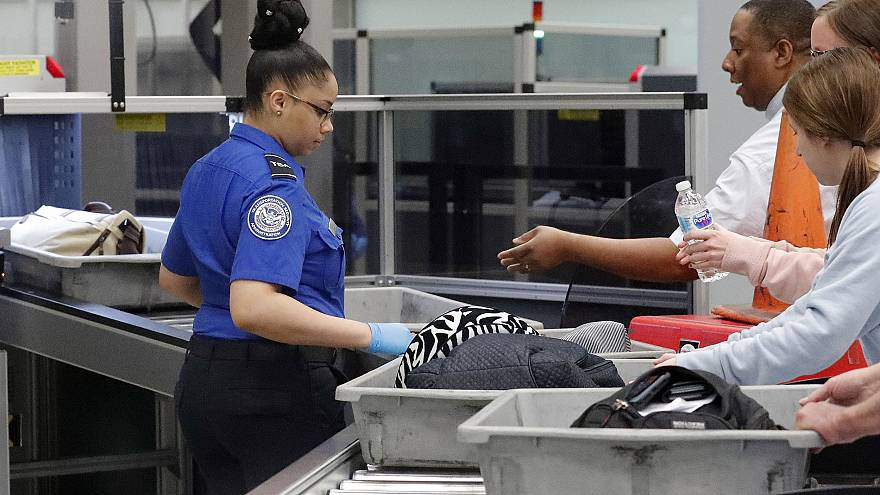 Image: A Transportation Security Administration employee helps air traveler