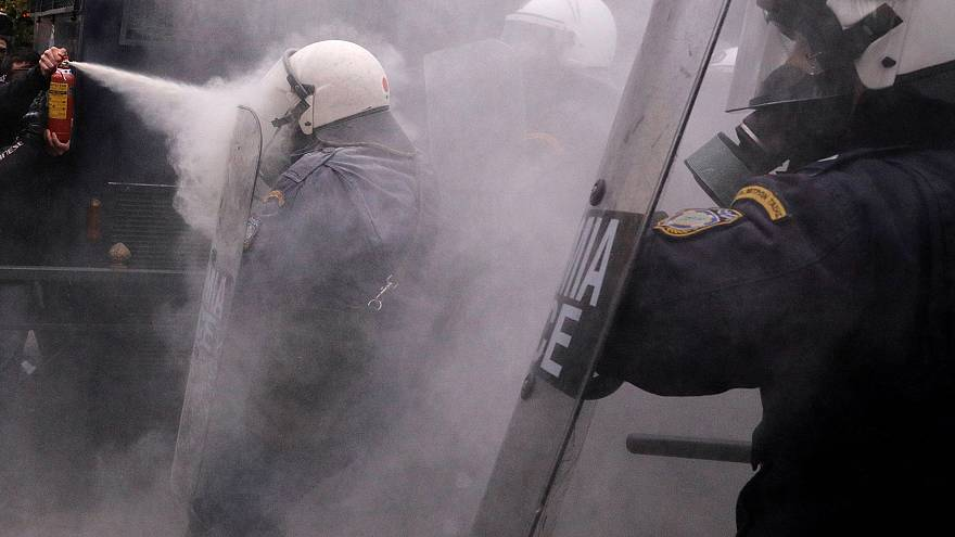 Image: A protester uses a fire extinguisher against riot police during clas