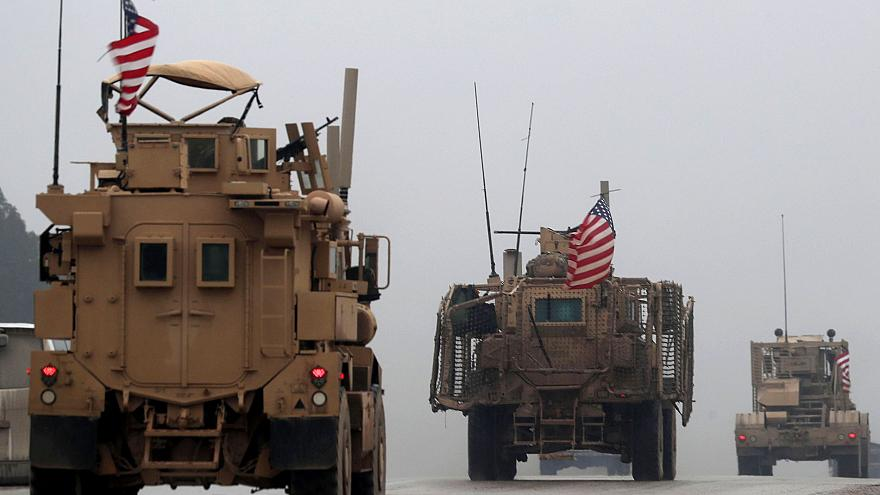 Image: A line of US military vehicles in Syria's northern city of Manbij