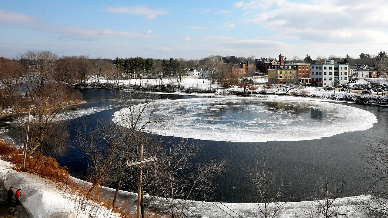 Image: A large, circular ice floe spins slowly in the Presumpscot River in