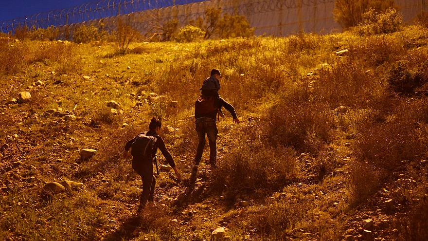 Image: Migrants from Honduras walk after crossing illegally from Mexico to