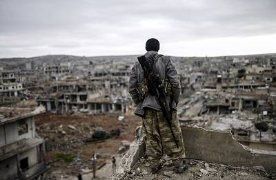 A Kurdish marksman stands atop a building as he looks at the destroyed Syrian town of Kobane in 2015. It had been recaptured from ISIS by Kurdish forces just days earlier.