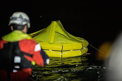 Rescuers drop a life raft after a rubber dingy carrying migrants capsized off the coast of Libya on Saturday.