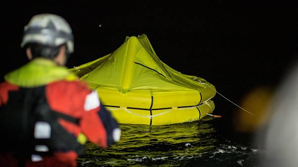 Image: Rescuers drop a life raft after a rubber dingy capsized off the coas