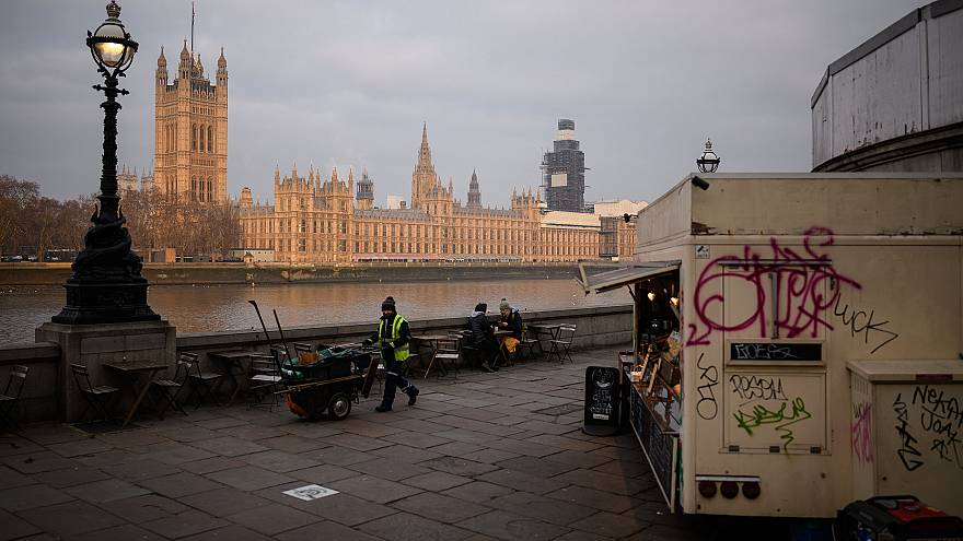Image: A street cleaner walks near the Houses of Parliament