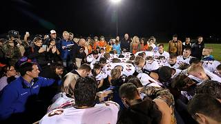 Image: Bremerton assistant football coach Joe Kennedy, obscured at center i