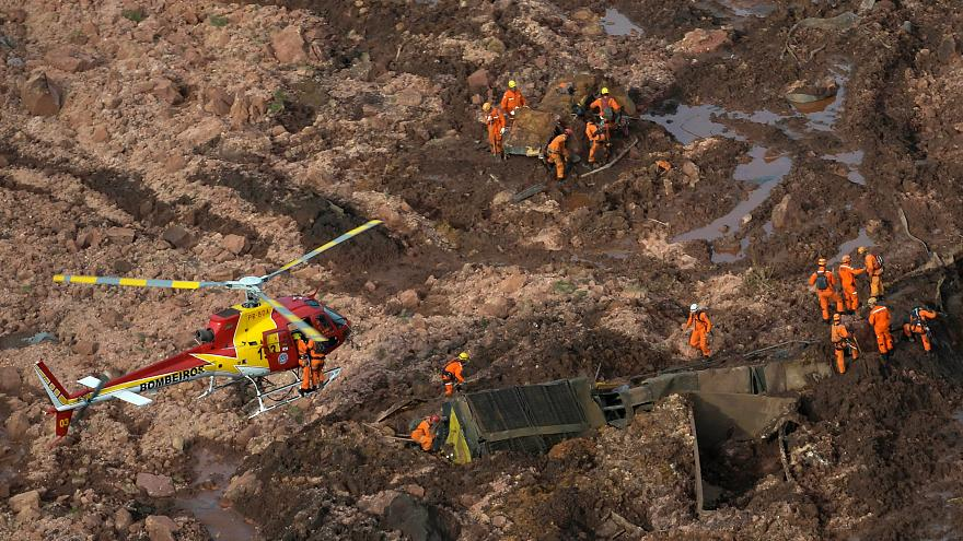 Image: Rescue crew work in a dam owned by Brazilian miner Vale SA that burs