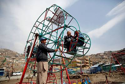 Children ride on a manually operated Ferris wheel in Kabul, Afghanistan.