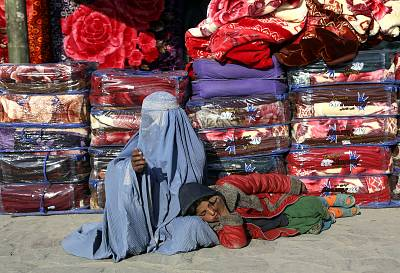 A woman and child beg on a sidewalk in Kabul, Afghanistan.