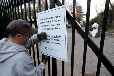 A Smithsonian National Zoo employee removes a closure sign after the zoo reopened at the end of the partial government shutdown on Jan. 28, 2019.