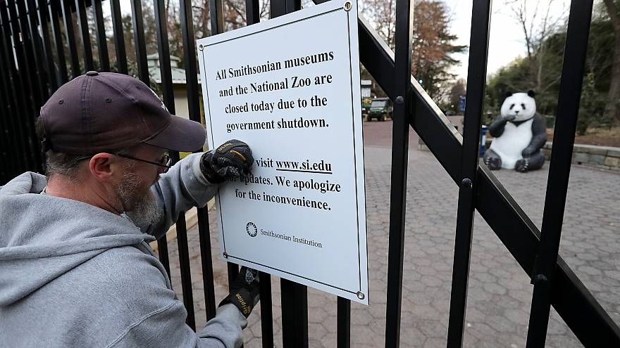 Image: A Smithsonian National Zoo employee removes a closure sign after the