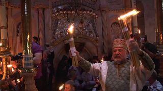 Cristãos acendem velas com fogo sagrado