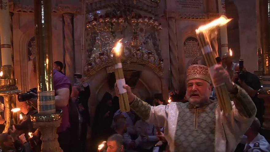 Christians light candles with holy fire