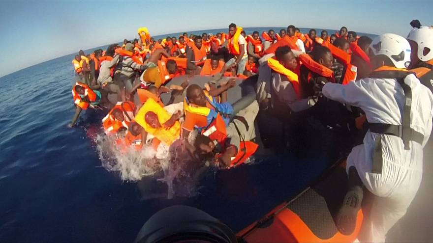 Rescuers jump into water to rescue migrants