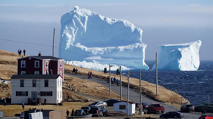 Kanada'da sahile sürüklenen buz dağı ziyaretçi akınına uğruyor