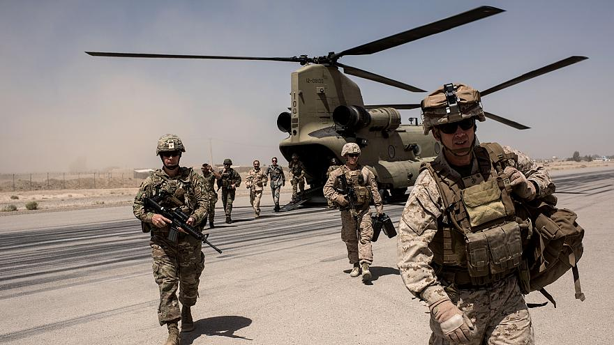 Image: U.S. troops walk off a helicopter at Camp Bost in Helmand Province,
