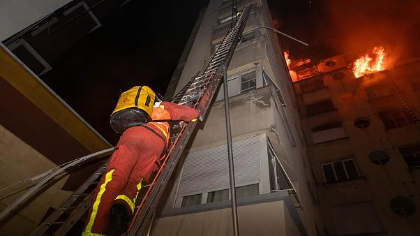 Image: A fireman climbs up a ladder to battle a fire burning in a building