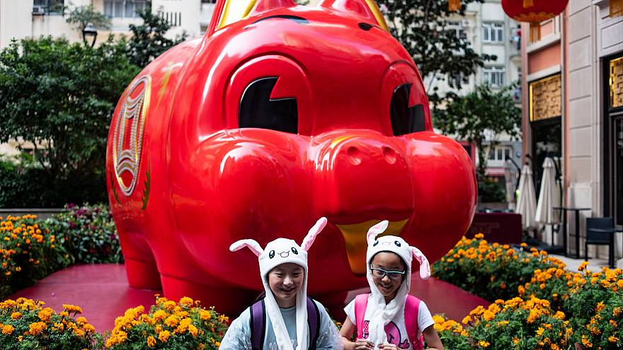 Image: Children in animal hats pose in front of a pig giant pig installatio