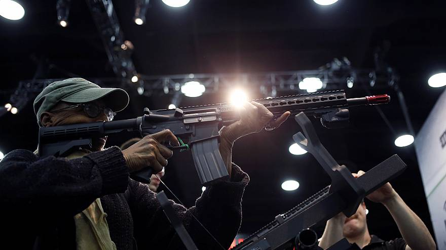 Image: An attendee holds an AR-15 style gun on the exhibit floor at the Nat
