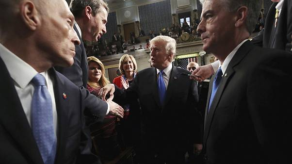 Image: Trump shakes hands as he leaves after delivering his first State of