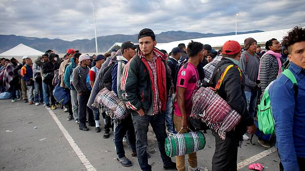 Image: Migrants wait in line to get into buses during their journey towards