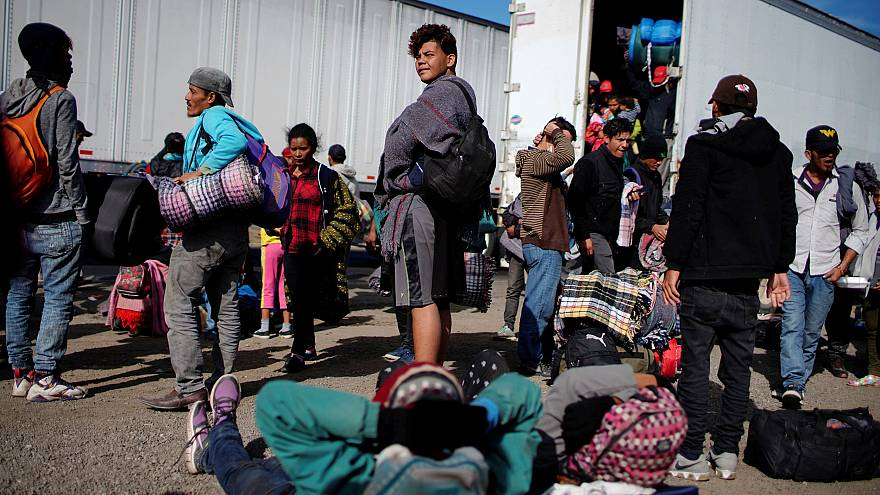 Image: Migrants rest beside a highway during their journey to the United St